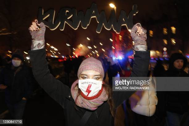Demonstrator wearing a face mask with a lighting bolt, the symbol of women's strike movement, and reading 'Get the fuck out' holds a placard reading...
