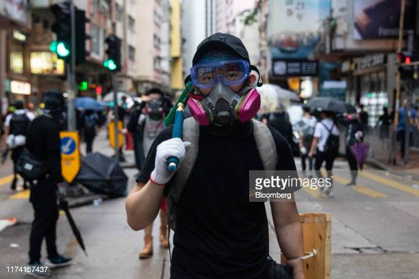 A demonstrator wearing a gas mask stands facing riot police during a protest in the Wan Chai district of Hong Kong China on Sunday Oct 6 2019...