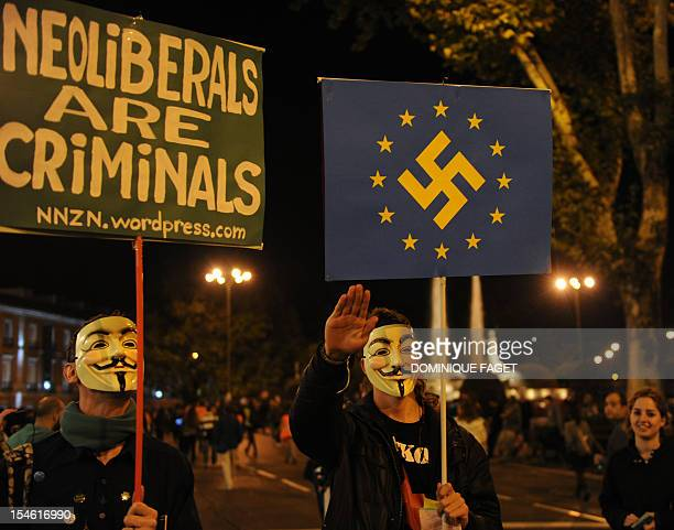 A demonstrator wearing a Guy Fawkes mask does the Nazi salute as he holds a placard depicting a EU flag with a swatiska in his centre as he takes...