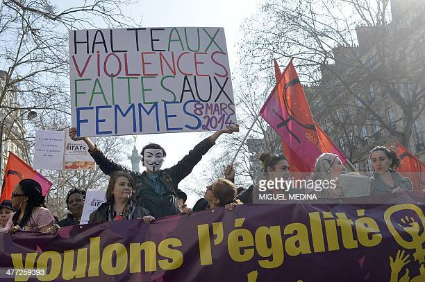 A demonstrator wearing a Guy Fawkes mask holds a sign reading 'Stop violence against women' as people take part in a march from the Place de la...