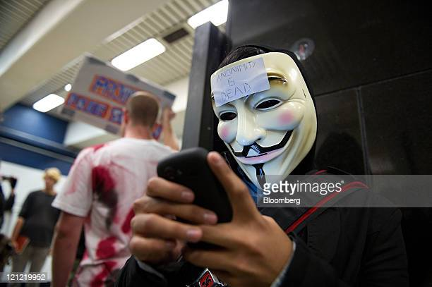 A demonstrator wearing a Guy Fawkes mask types on his mobile phone as he joins members of the Internet group known as Anonymous demonstrate in the...