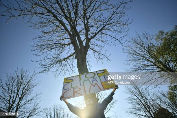 A demonstrator wearing a GuyFawkesmask holds up a poster reading 'Stop Climate Crime' as he takes part in a socalled Climate March against...