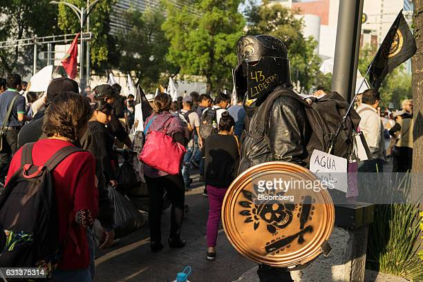 A demonstrator wearing a helmet and shield looks on as others march during a protest against the gasoline price hike in Mexico City Mexico on Monday...