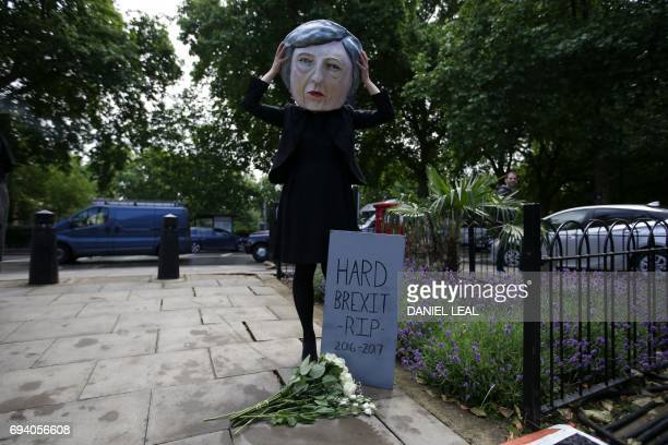 A demonstrator wearing a mask depicting Britain's Prime Minister and leader of the Conservative Party Theresa May poses with a mock gravestone...