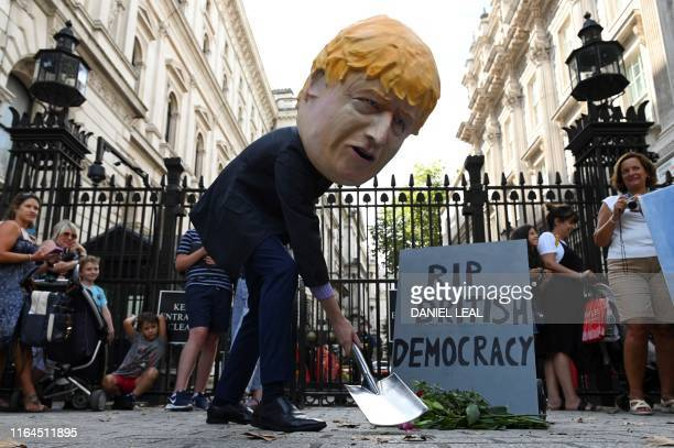 TOPSHOT A demonstrator wearing a mask depicting Britain's Prime Minister Boris Johnson and a mock gravestone inscribed with the words RIP British...