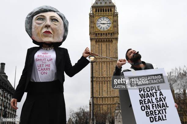 A demonstrator wearing a mask depicting Britain's Prime Minister Theresa May protests against the United Kingdom's triggering of Article 50 outside...