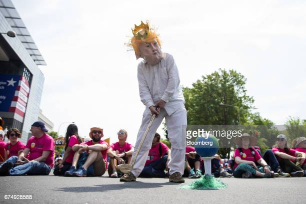 A demonstrator wearing a mask in the likeness of US President Donald Trump prepares to swing a golf club at a globe during the People's Climate...