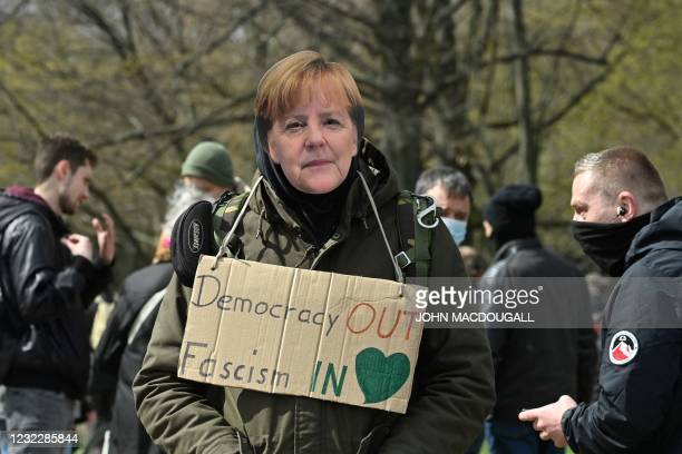 """Demonstrator wearing a mask of German Chancellor Angela Merkel wears a placard around his neck reading """"democracy out, fascism in"""" during a..."""