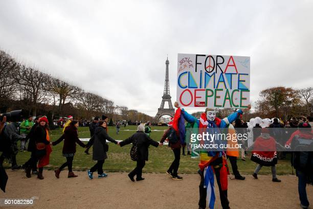 TOPSHOT A demonstrator wearing a mask of the Anonymous group holds a banner reading 'For a climate of Peace' during a rally called by several Non...