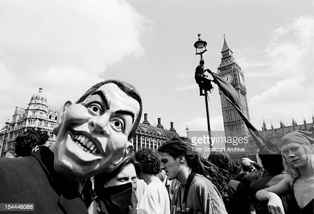 A demonstrator wearing a mask of Tony Blair takes part in a May Day anticapitalist protest in Parliament Square in front of Big Ben London 1st May...