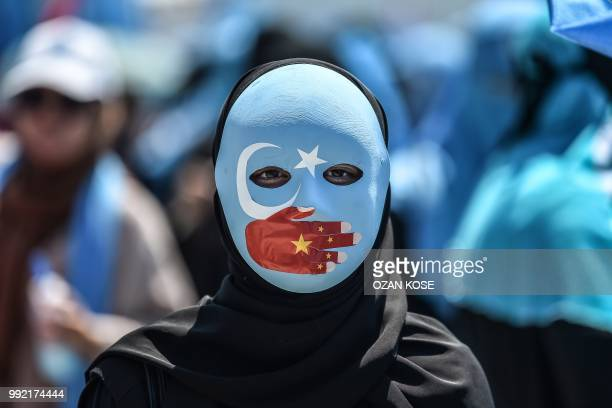 TOPSHOT A demonstrator wearing a mask painted with the colours of the flag of East Turkestan and a hand bearing the colours of the Chinese flag...