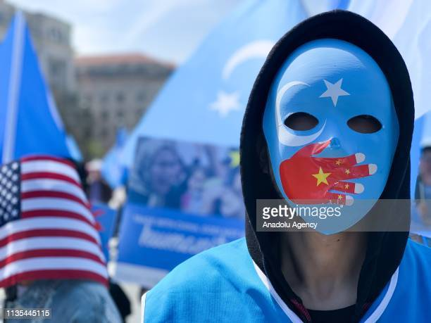 A demonstrator wearing a mask takes part in a protest against Chinas human rights abuses against Uighur Muslims in Xinjiang province calling on US...