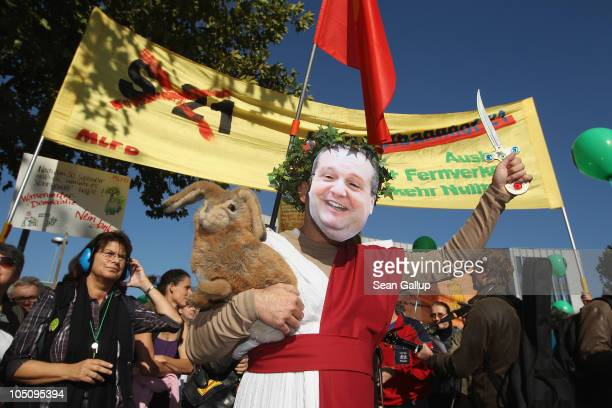 A demonstrator wearing a mask to look like BadenWuerttemberg Governor Stefan Mappus joins tens of thousand of activists marching to protest the...
