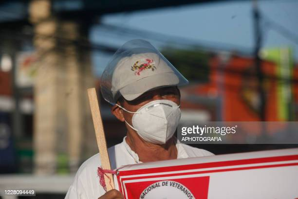 A demonstrator wearing a protective mask and a face shield holds a banner during a veterans protest from the former guerrilla Frente Farabundo Marti...