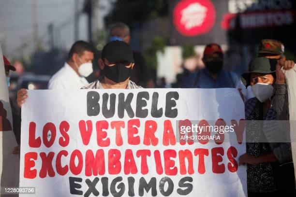 A demonstrator wearing a protective mask holds a sign during a veterans protest from the former guerrilla Frente Farabundo Marti Para La Liberacion...