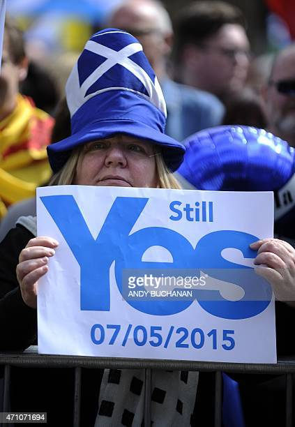 A demonstrator wearing a Saltire themed hat holds a placard reading Still Yes referring to the date of the UK general election during a...