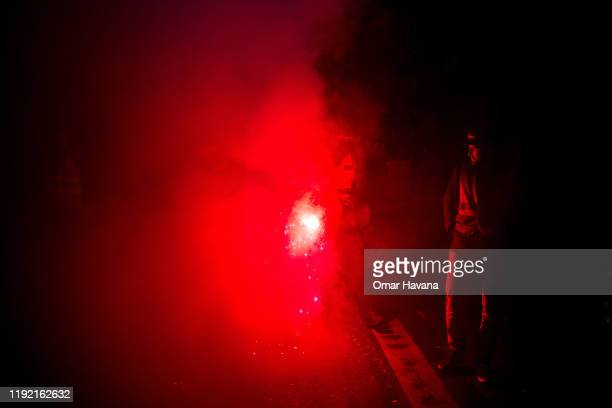A demonstrator wearing a SCNF vest walks holding a red flare during the first day of an indefinite general strike on December 05 2019 in Paris France...