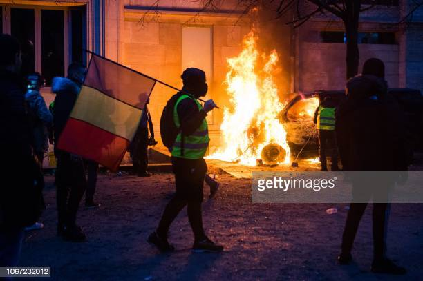 A demonstrator wearing a Yellow vest holds a French flag as a vehicle is burning on the Tuileries Garden in front of the Musee de l'Orangerie during...
