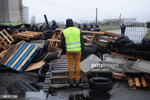 A demonstrator wearing a yellow vest stands behind barricades blocking a road near the oil depot of La Rochelle southwestern France on December 3...