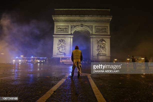 A demonstrator wearing a Yellow vest stands in front of the Arc de Triomphe on the Champs Elysees avenue in Paris during a protest of Yellow vests...