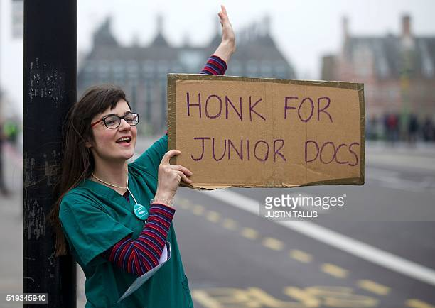 Demonstrator wearing doctor's scrubs holds a placard as she protests during a Junior Doctors' strike outside St Thomas' Hospital in central London on...