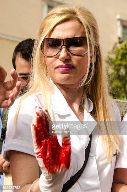 Demonstrator wearing painted red gloves symbolizing blood Greek nurses demonstrated in front of the Greek parliament commemorating the International...