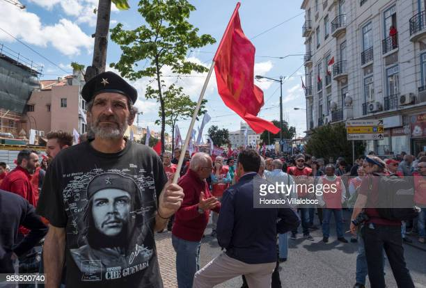 A demonstrator wears a Che Guevara Tshirt while hoisting a red flag during the parade to commemorate the International Workers' Day staged by the...