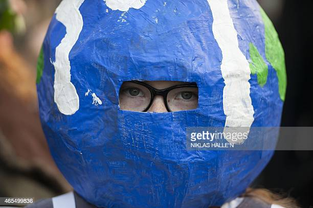 A demonstrator wears a earthshaped headdress as she takes part in The People's Climate march in central London on March 7 2015 Around 5000 protesters...