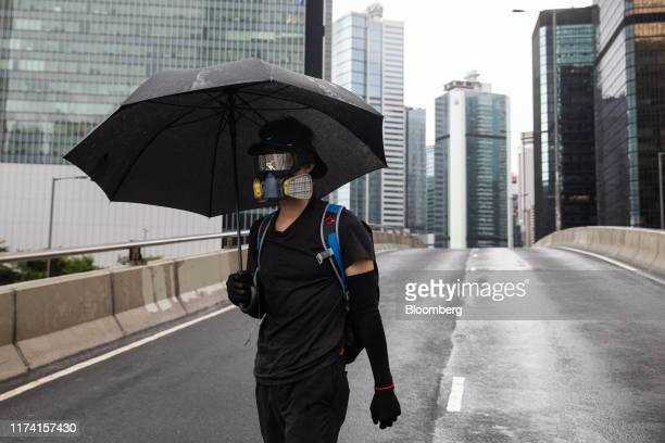 A demonstrator wears a face mask and carries an umbrella during a protest in Admiralty district of Hong Kong China on Sunday Oct 6 2019 Violence...