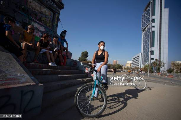Demonstrator wears a face mask as a precautionary measure against the spread of the new coronavirus, COVID-19, during a protest -with little...