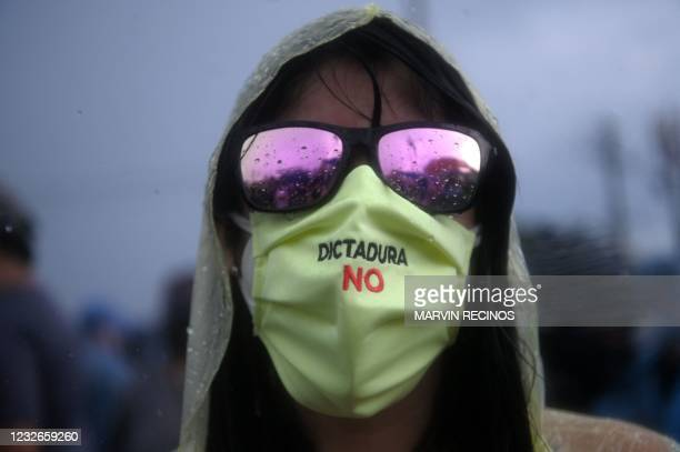 Demonstrator wears a face mask reading Dictatorship not during a protest against the latest measures taken by the Legislative Assembly, including the...