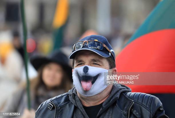 Demonstrator wears a face mask with an image of a dog's snout during an anti-lockdown protest in Cathedral Square in Vilnius on March 20 during the...