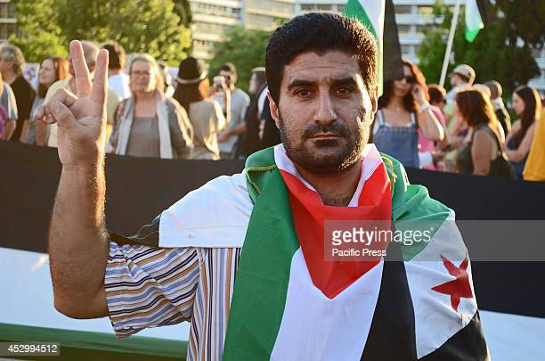 Demonstrator wears a flag of Palestine as a cape while making the victory sign. Left wing party supporters together with people from Palestine...