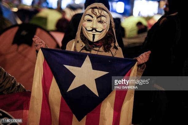 A demonstrator wears a Guy Fawkes mask and holds a Catalan proindependence Estelada flag during a Million Mask March organised by Anonymous and other...