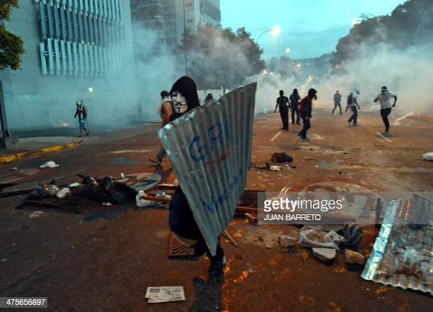 A demonstrator wears a Guy Fawkes mask as he holds a metal sheet during an antigovernment protest in Caracas on February 28 2014 Hundreds of people...