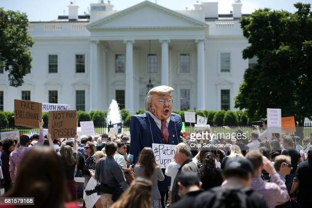 A demonstrator wears a large effigy of President Donald Trump during a protest rally against President Donald Trump's firing of Federal Bureau of...