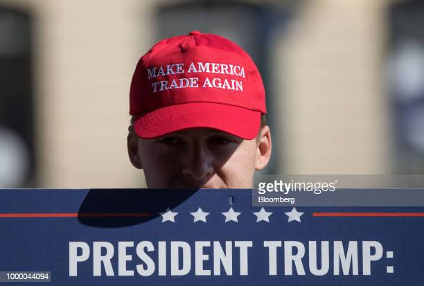 A demonstrator wears a 'Make America Trade Again' hat close to the Presidential Palace in Helsinki Finland on Monday July 16 2018 US President Donald...
