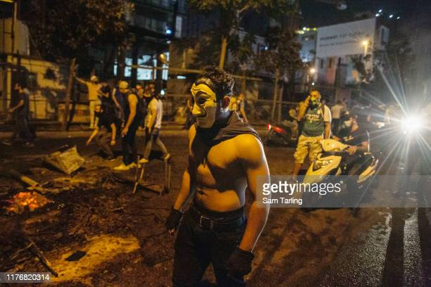 Demonstrator wears a mask and cape at a protest in downtown Beirut, on October 18, 2019 in Beirut, Lebanon. Protests flared this week after the...