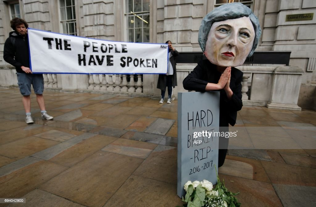 TOPSHOT - A demonstrator wears a mask depicting Britain's Prime Minister and leader of the Conservative Party Theresa May, poses with a mock gravestone bearing the words 'Hard Brexit, RIP', during a protest photocall near the entrance 10 Downing Street in central London on June 9, 2017 as results from a snap general election show the Conservatives have lost their majority. British Prime Minister Theresa May faced pressure to resign on June 9 after losing her parliamentary majority, plunging the country into uncertainty as Brexit talks loom. The pound fell sharply amid fears the Conservative leader will be unable to form a government and could even be forced out of office after a troubled campaign overshadowed by two terror attacks. / AFP PHOTO / Adrian DENNIS