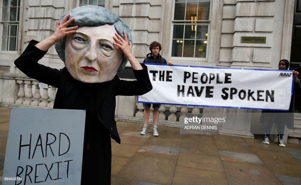 A demonstrator wears a mask depicting Britain's Prime Minister and leader of the Conservative Party Theresa May, poses with a mock gravestone bearing the words 'Hard Brexit, RIP', during a protest photocall near the entrance 10 Downing Street in central London on June 9, 2017 as results from a snap general election show the Conservatives have lost their majority. British Prime Minister Theresa May faced pressure to resign on June 9 after losing her parliamentary majority, plunging the country into uncertainty as Brexit talks loom. The pound fell sharply amid fears the Conservative leader will be unable to form a government and could even be forced out of office after a troubled campaign overshadowed by two terror attacks. /
