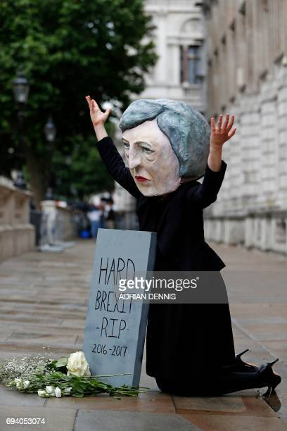 A demonstrator wears a mask depicting Britain's Prime Minister and leader of the Conservative Party Theresa May as they pose with a mock gravestone...