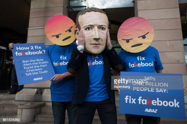 A demonstrator wears a mask depicting Facebook Inc Chief Executive Officer Mark Zuckerberg center as he stands with demonstrators wearing angry emoji...