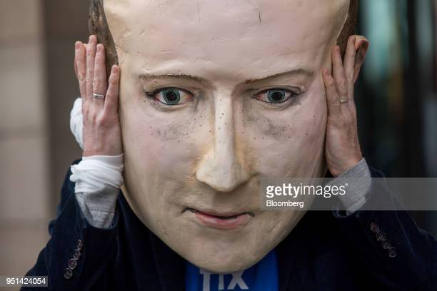 A demonstrator wears a mask depicting Facebook Inc Chief Executive Officer Mark Zuckerberg outside the venue of a UK parliamentary committee hearing...