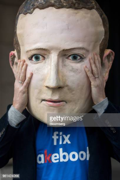Demonstrator wears a mask depicting Facebook Inc. Chief Executive Officer Mark Zuckerberg outside the venue of a U.K. Parliamentary committee hearing...