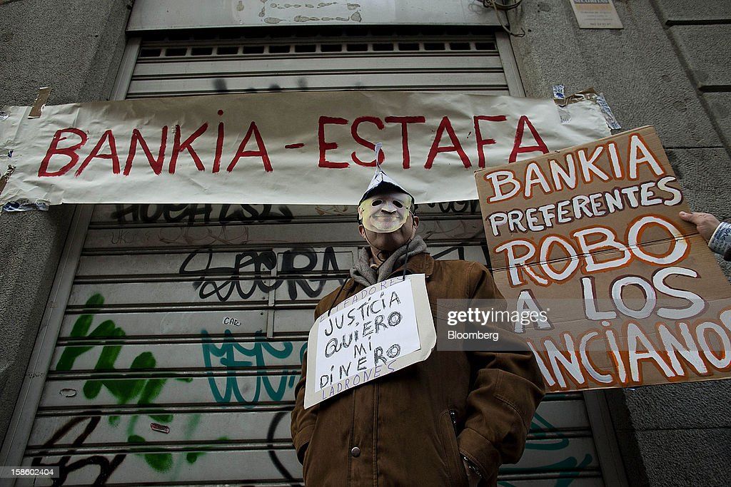 A demonstrator wears a mask during a protest against Rodrigo Rato, former managing director of the International Monetary Fund and ex-chairman of Bankia Group, as he testifies at Spain's national court in Madrid, Spain, on Thursday, Dec. 20, 2012. Rato who led the seven-way savings bank merger in 2010 that formed Bankia, has appeared before lawmakers probing how the lender that was nationalized after seeking 23.5 billion euros ($28.5 billion) of state aid helped trigger a new stage of Europe's debt crisis. Photographer: Angel Navarrete/Bloomberg via Getty Images