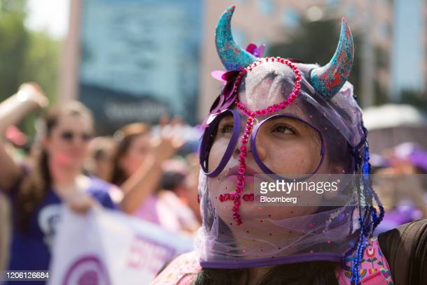 A demonstrator wears a mask during a rally on International Women's Day in Mexico City Mexico on Friday March 8 2020 The United Nations first...