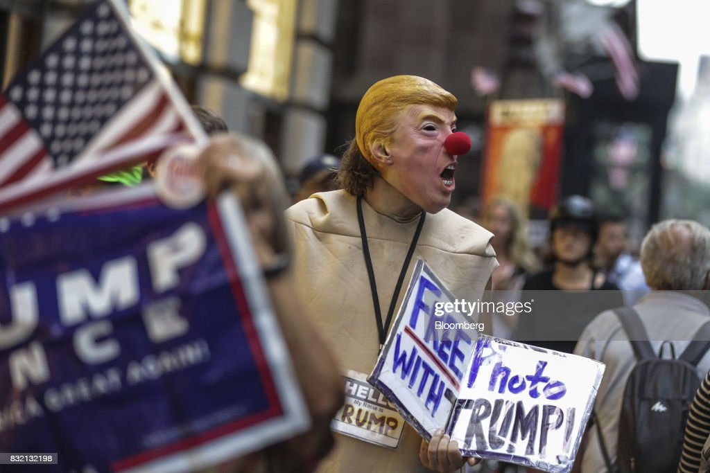 A demonstrator wears a mask in the likeness of U.S. President Donald Trump during the 'Defend DACA & TPS' rally outside of Trump Tower in New York, U.S., on Tuesday, Aug. 15, 2017. A day after belatedly faulting white supremacists for deadly clashes in Virginia, President Donald Trump returned to his controversial position that there was 'blame on both sides' for the weekend violence, saying that liberal counter-protesters also bore responsibility. Photographer: Jeenah Moon/Bloomberg via Getty Images