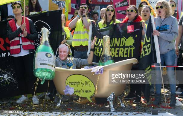 A demonstrator wears a mask of German Interior Minister Seehofer and sits in a bathtub reading Champagne for All as public sector workers demonstrate...
