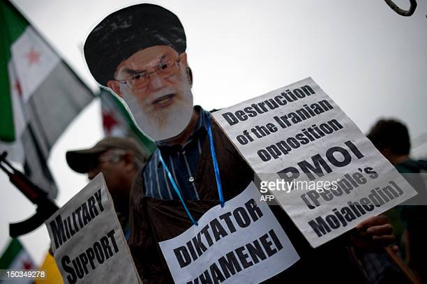 A demonstrator wears a mask of Iran's Supreme Leader Ali Ayatollah Khamenei during a rally of opponents to the governments of Syria and Iran on...
