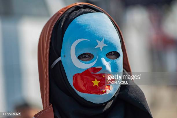 TOPSHOT A demonstrator wears a mask painted with the colours of the flag of East Turkestan and a hand bearing the colours of the Chinese flag as she...
